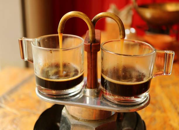 aromatischen kaffee rieselt aus mini retro brauen topf in ein paar demitasse glaspokale - mokkatassen stock-fotos und bilder