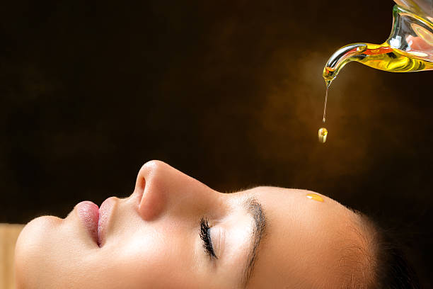 Aromatic oil dripping on female face.​​​ foto