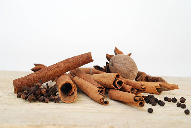 Aromatic Spices on a Wooden Cutting Board with a White Background A loose pile of cinnamon sticks, whole cloves, cardamon, black pepper corns, whole nutmeg, and star anise on wood, with a white background.  Warm tones of brown and orange. clove spice stock pictures, royalty-free photos & images