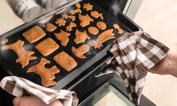 Aromatic sweet gingerbreads on baking sheet in an open hot steaming oven stock photo