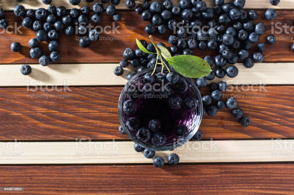 Aronia spilled on table with glass of aronia juice stock photo