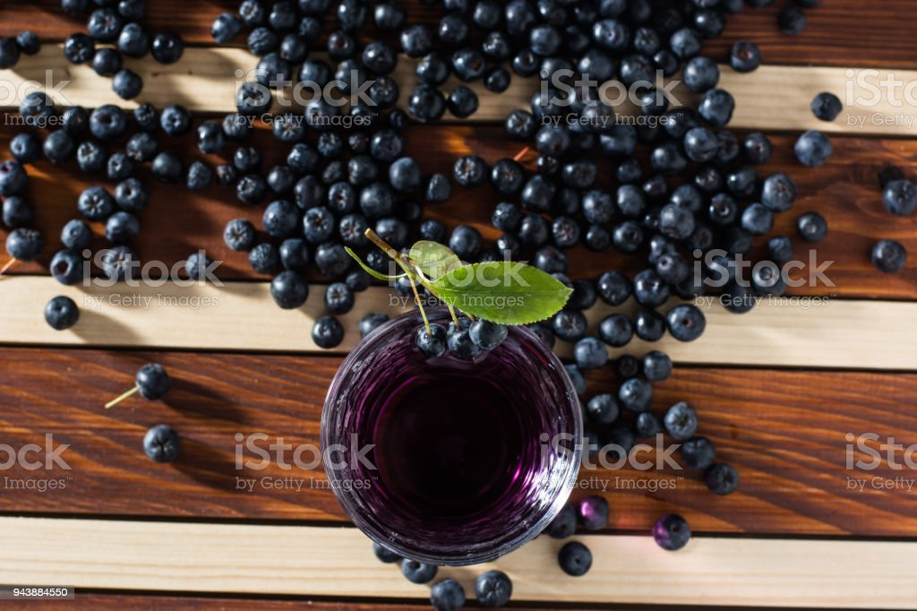 Aronia spilled on wooden table with glass of aronia juice stock photo
