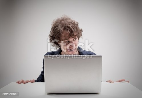 istock aroused man with tongue stuck out watching porn 832655616