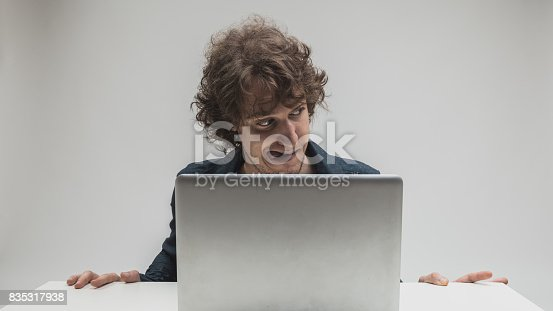 istock aroused man with tongue stuck out watching porn 835317938