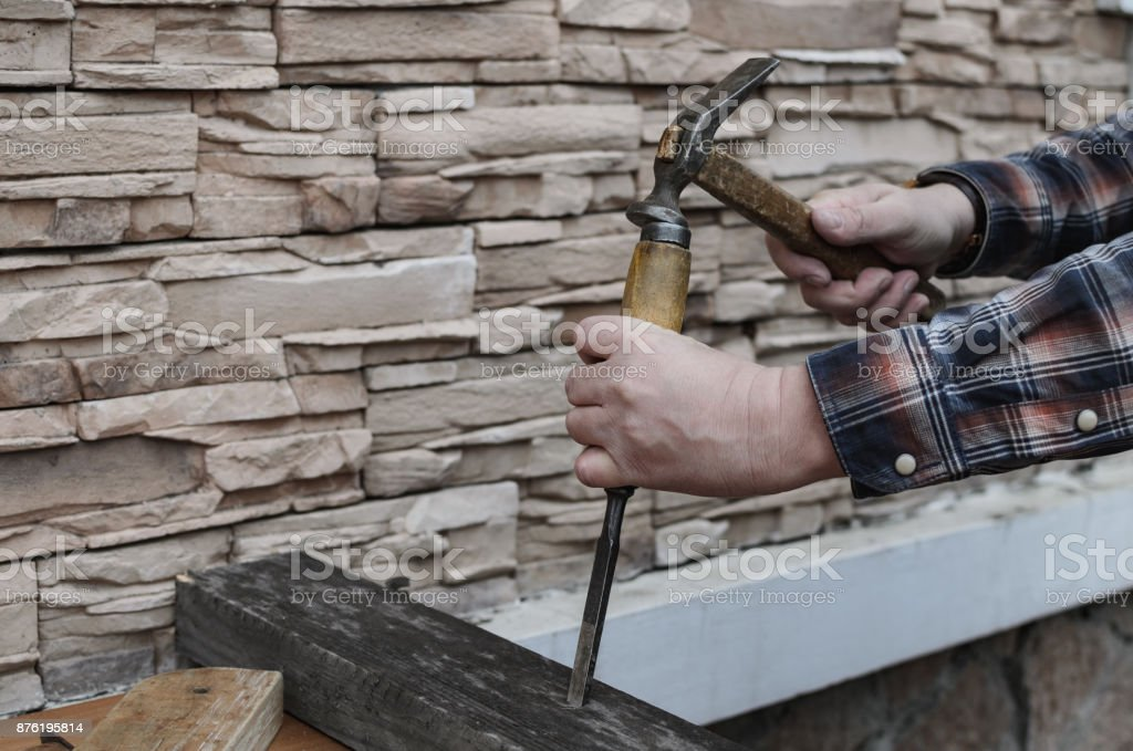 Сarpenter working with a hammer, chisel and wood carving tools stock photo