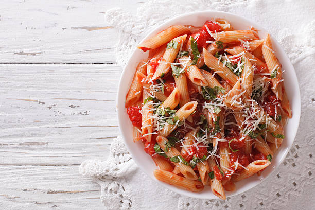 Arrabiata pasta penne with Parmesan cheese. Horizontal top view Arrabiata pasta penne with Parmesan cheese on a plate. horizontal top view penne stock pictures, royalty-free photos & images