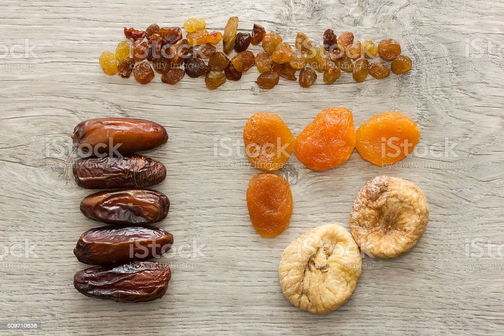 Arranged dried fruits on wooden table stock photo