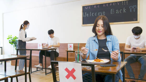 Arrangement blank space table to prevent and stop coronavirus spread by social distancing concept. Asian woman and asia people eating food alone at table in reopening restaurant after lockdown measure stock photo