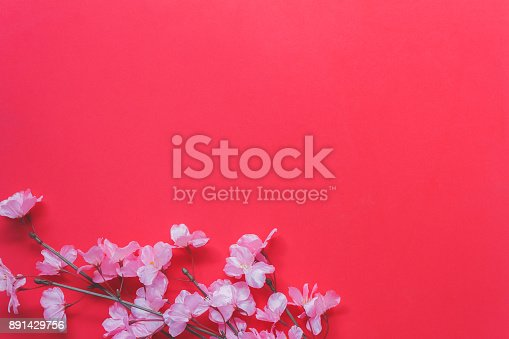 istock arrangement decoration Chinese new year & lunar festival concept background.Beautiful pink blossom on modern red wood wallpaper at home office desk.Free space for creative design text and wording. 891429756