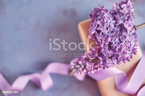 Arrangement for Mother's day with lilac flowers and a wrapped gift
