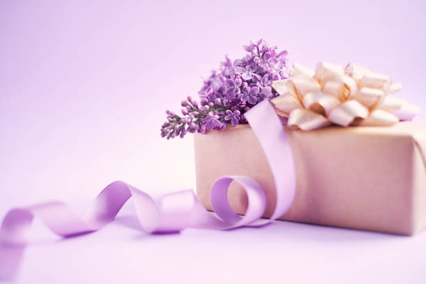Arrangement for Mother's day with lilac flowers and a wrapped gift stock photo