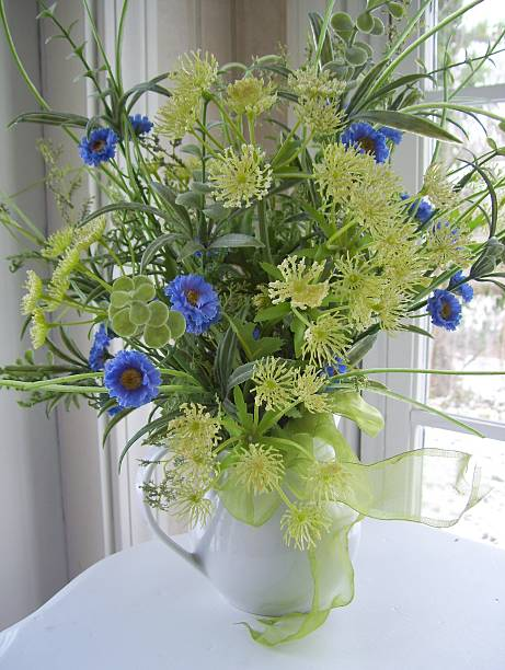 Arrangement of Blue and Yellow Flowers in White Pitcher stock photo
