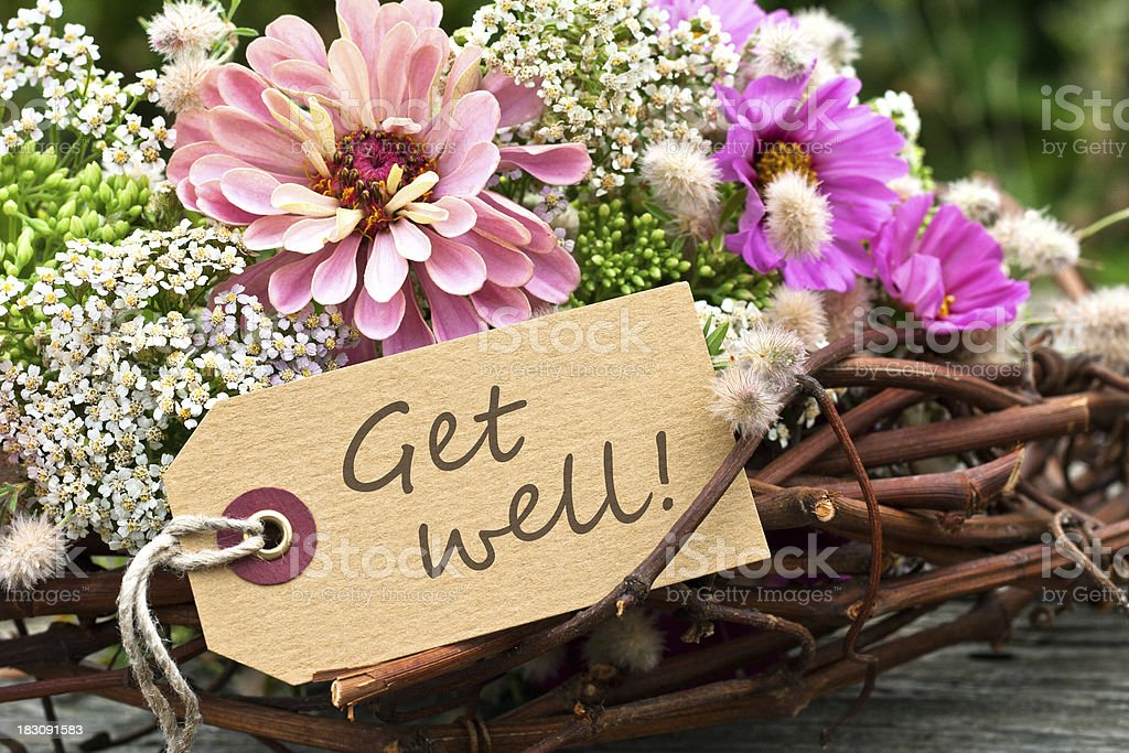 Arrangement of flowers and twigs with Get Well message stock photo