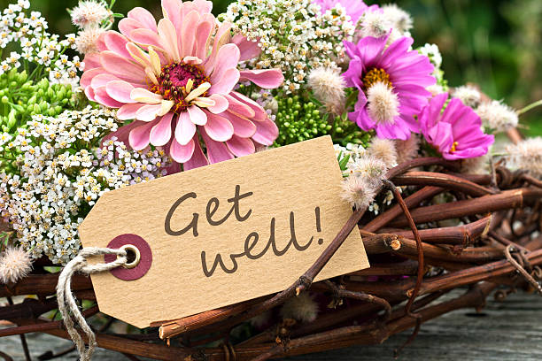 Arrangement of flowers and twigs with Get Well message​​​ foto