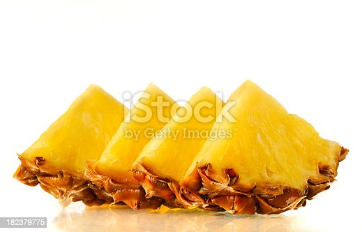 Slices of fresh pineapple on a reflective surface. Shallow DoF.
