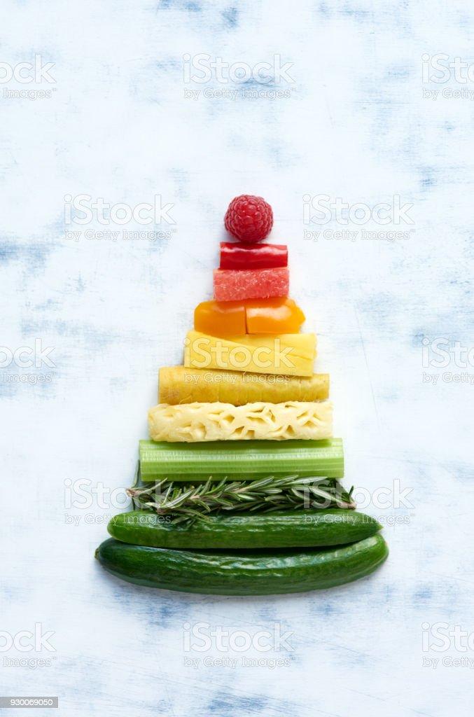 Anordnung von Obst und Gemüse in Regenbogen Farbverlauf in Form eines Dreiecks – Foto
