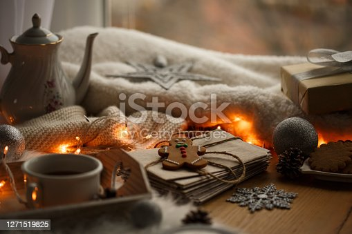 Shot of small arrangement of letters for Santa next to some Christmas knick-knacks like fairy lights, ornaments, warm tea, Gingerbread man cookie, and warm tea on a wooden table.