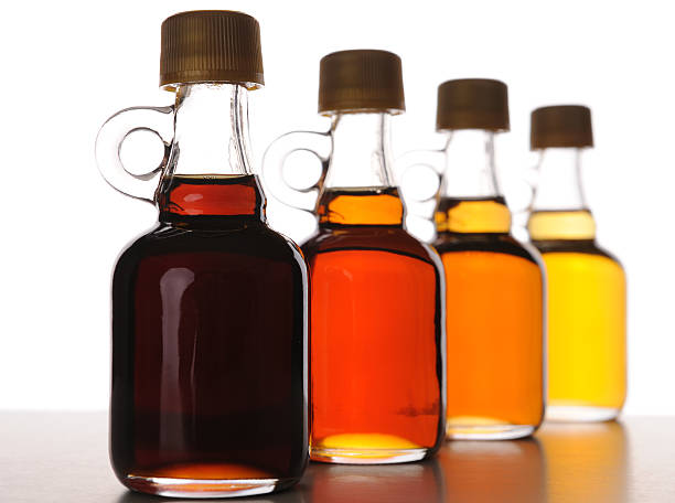 arrangement of maple syrup bottles with various grades - maple syrup stock photos and pictures