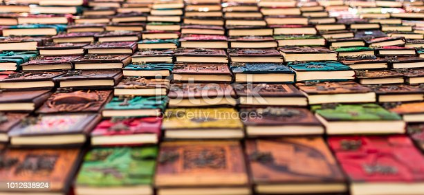 Panoramic color image depicting a large selection of colorful hardback books in a row. Selective focus means focus is sharp only on a few of the books,