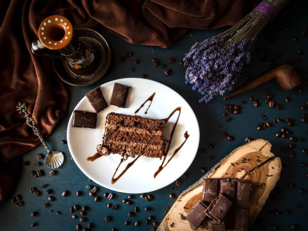 arrangement of slice chocolate cake and pieces of coffee and chocolate on dark background. - chocolate mousse stock photos and pictures
