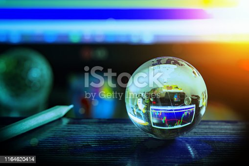 Arrangement of World globe crystal glass and pencil on charts stock data on computer screen background. Global business on financial concept. World wide technology with copy space.