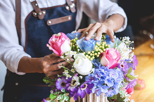 istock Arranging artificial flowers vest decoration at home, Young woman florist work making organizing diy artificial flower, craft and hand made concept 1054918150