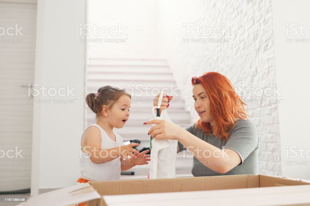 Mother with her daughter arranging clothes from cardboard box