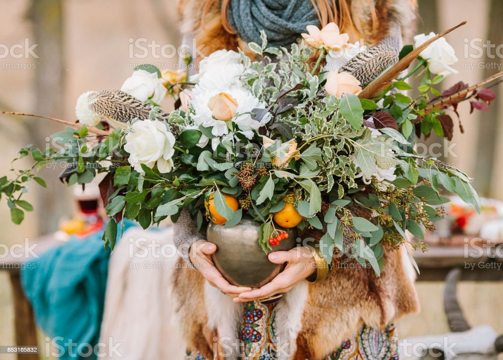 arranging, fall, style concept. girl wearing ornamental dress and fox jacket holding vase with wondreful autumnal bunch composed of various flowers and decorated with leaves of eucaliptus and rosebush stock photo