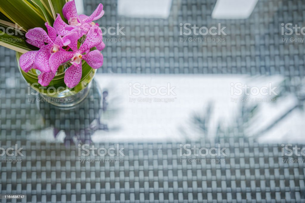 Arranging orchids in a glass vase in beach oriental hospitality...