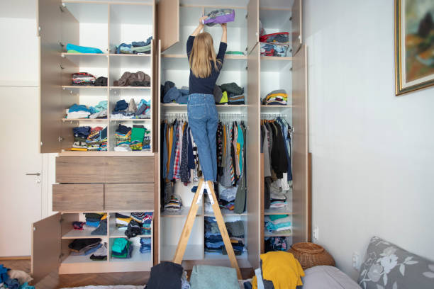 Arranging wardrobe during home isolation Young woman cleanis up the mess in the closet. arrangement stock pictures, royalty-free photos & images