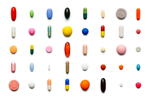 Array of large group of assorted capsules and pills on white background. High resolution image. stock photo