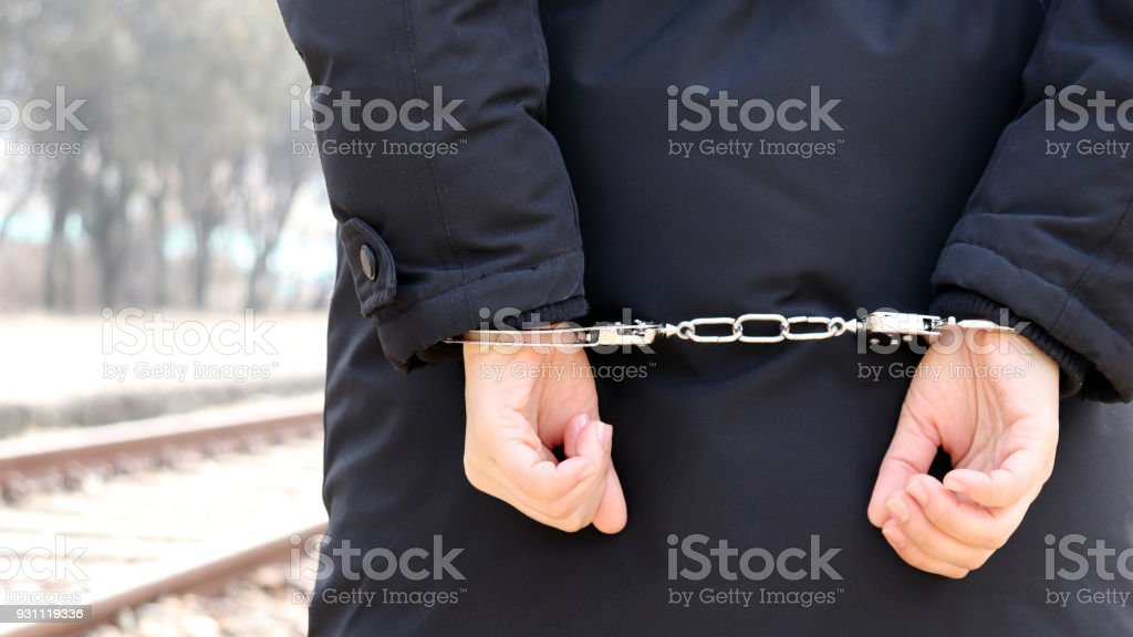 Arrest and handcuff a suspect. Appearance from behind of criminal. stock photo