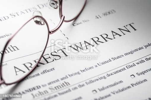 istock Arrest Warrant document with reading glasses 1307834862