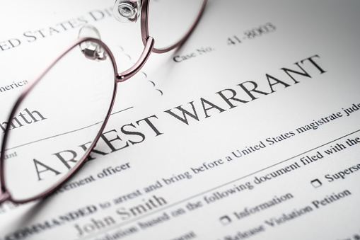 Arrest Warrant document with reading glasses