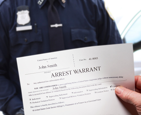 Arrest Warrant with man holding paper next to police officer