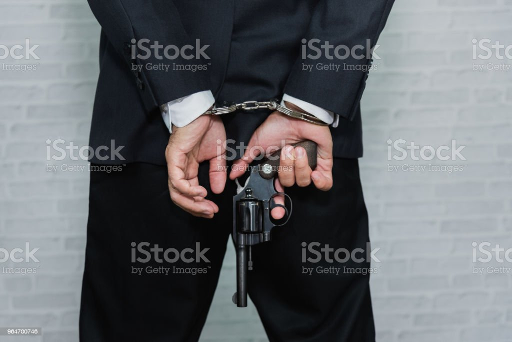 Arrested businessman in handcuffs and hold gun with hands behind back royalty-free stock photo
