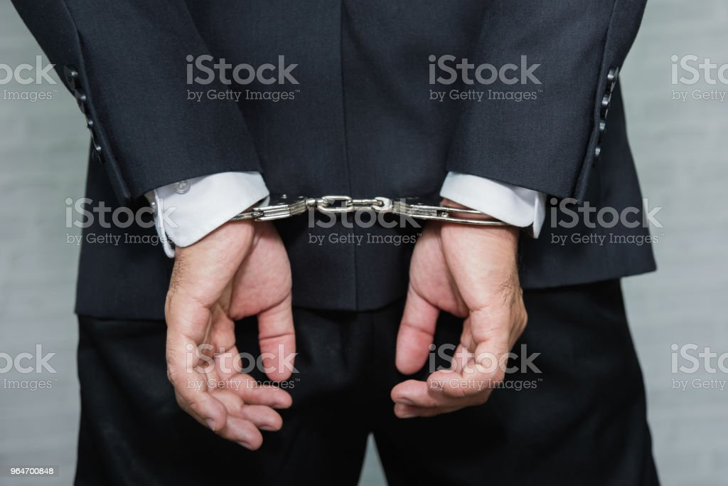 Arrested businessman in handcuffs with hands behind back royalty-free stock photo