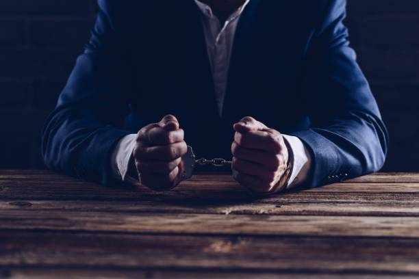 Arrested male businessman with handcuffs stock photo