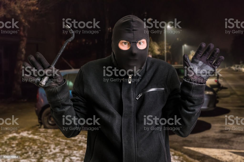 Arrested masked thief in balaclava with crowbar and raised arms stock photo