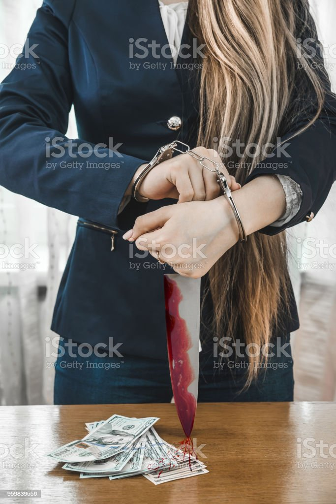 Arrested woman in handcuffs with knife in blood stock photo