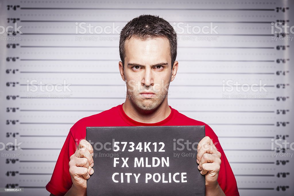Arrested young man standing in front of jail height chart stock photo