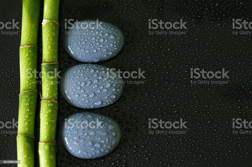 arrière plan noir avec branche de Bambou sur la gauche et galets zen gris avec gouttes d'eau stock photo