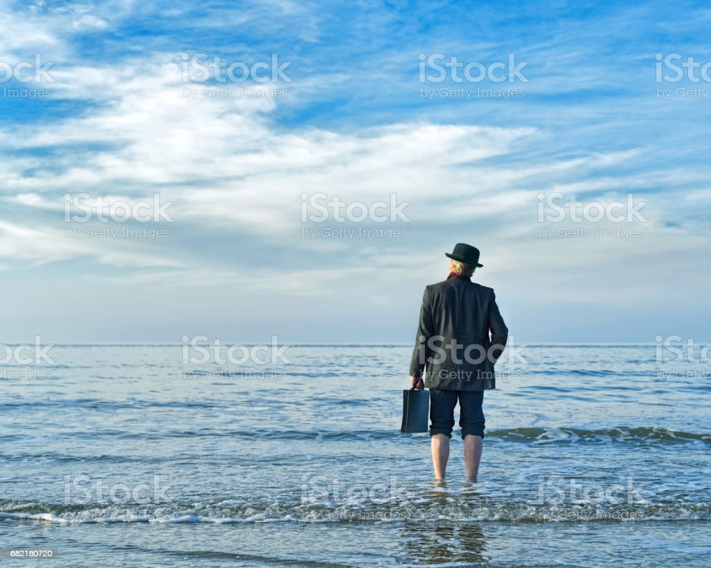 Arrival of businessman at beach standing barefoot in water holding briefcase in hand stock photo