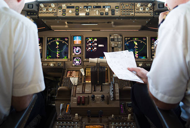 Arrival Route Check First Officer of a modern commercial airplane studying approach charts for destination pilot stock pictures, royalty-free photos & images