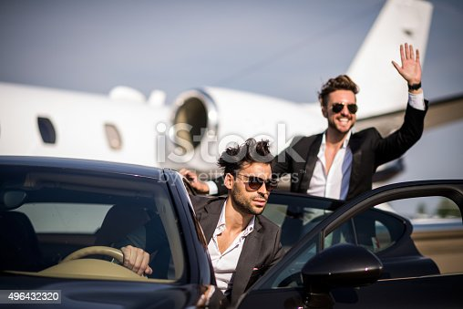 Driver and famous person exiting the black car upon arrival at the airport track. They are both nicely dressed and wearing sunglasses while the man in the back is waving to someone. Private jet airplane is in the background.