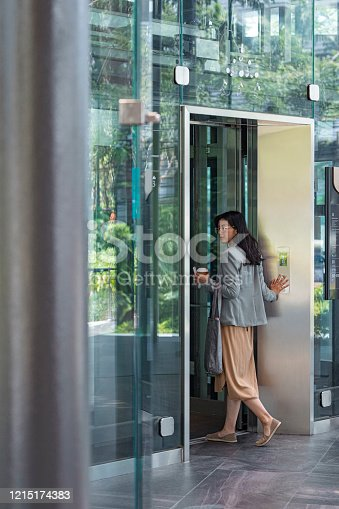 Asian businesswoman entering an elevator in an office building.