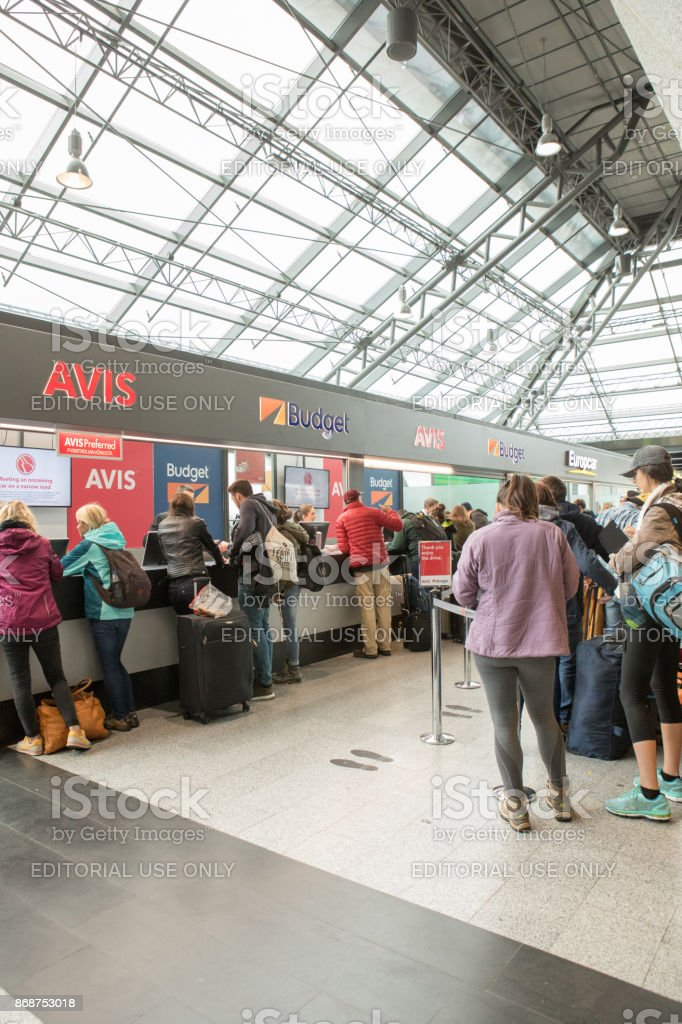 Os passageiros a esperar na fila para alugar carros no Aeroporto Internacional de Keflavík, Islândia - foto de acervo