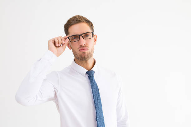 Arrogant business man adjusting glasses and looking at camera stock photo