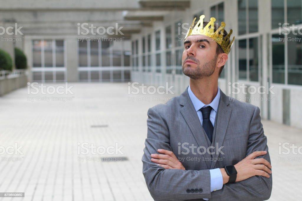 Empresário arrogante com uma coroa no espaço de escritório foto royalty-free