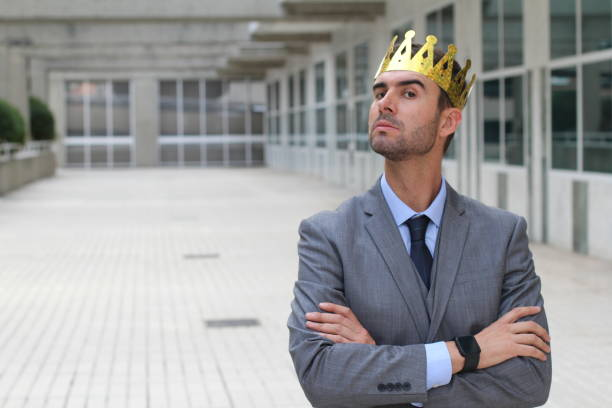 arrogant businessman with a crown in office space - arrogance stock pictures, royalty-free photos & images